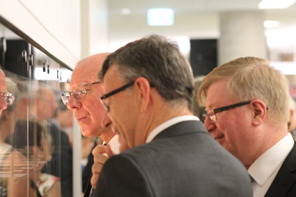 The Governor, Archbishop and Dr Thompson examine exhibits in library showcases.