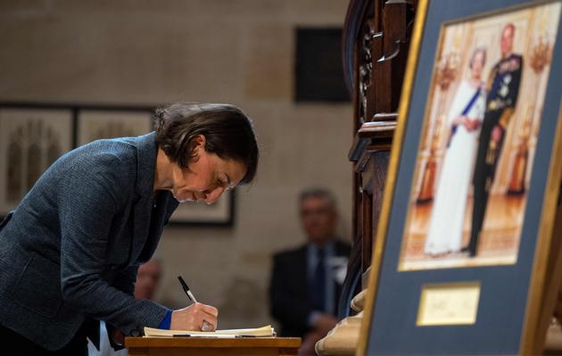 The Premier signs the condolence book.