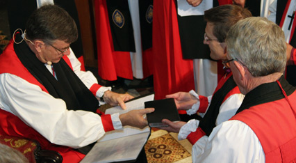Archbishop Davies hands Bishop Stead a Bible, during the consecration ceremony.